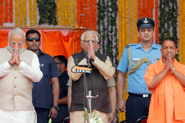 Narendra Modi, left, Uttar Pradesh governor Ram Naik and Yogi Adityanath, right, greet a gathering before Adityanath takes an oath as the new leader of Uttar Pradesh on March 19 [Pawan Kumar/Reuters]