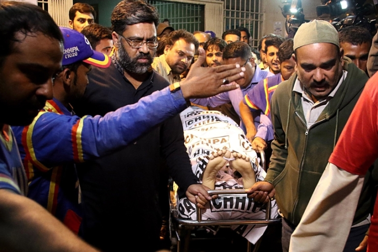 Rescue workers move the body of Taimur Abbas, a cameraman of Pakistan's Samaa TV who was killed by gunmen in Karachi in February [Shahzaib Akber/EPA]