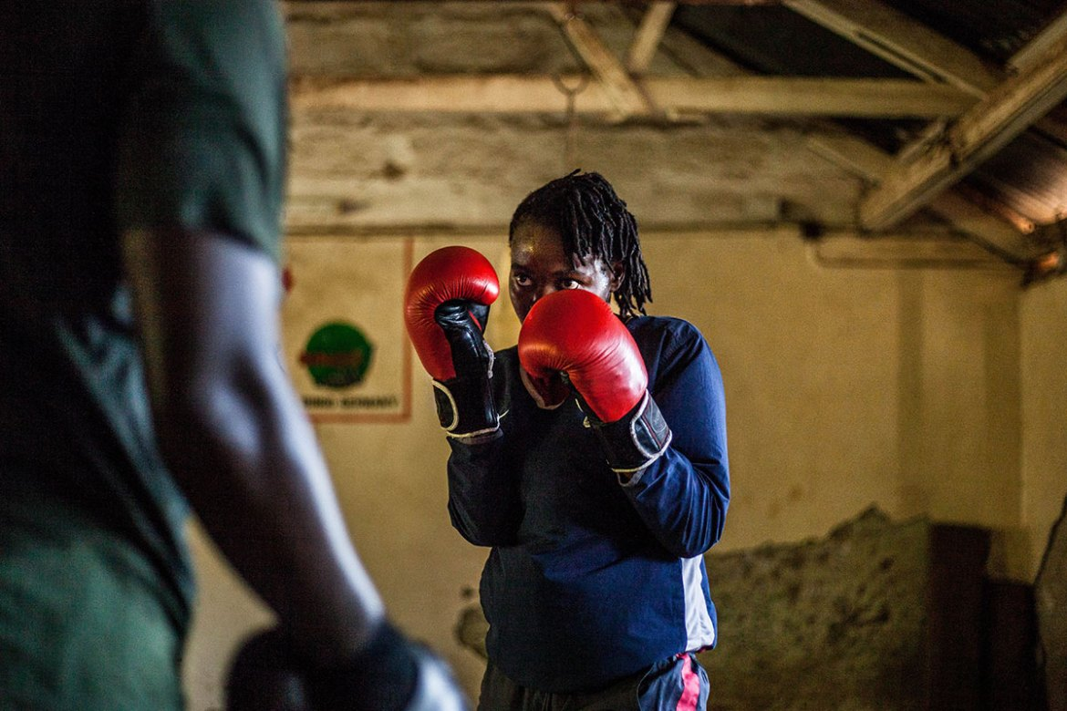 Damaris, a coach in Kariobangi, trains with professional male boxers in the early morning hours at Kariobangi Community Hall, before leading a school outreach session in the community. Box Girls Kenya believes that sports and physical activity programmes can be used as a platform to provide girls and women with an education in life skills. [Natalia Jidovanu/Al Jazeera]