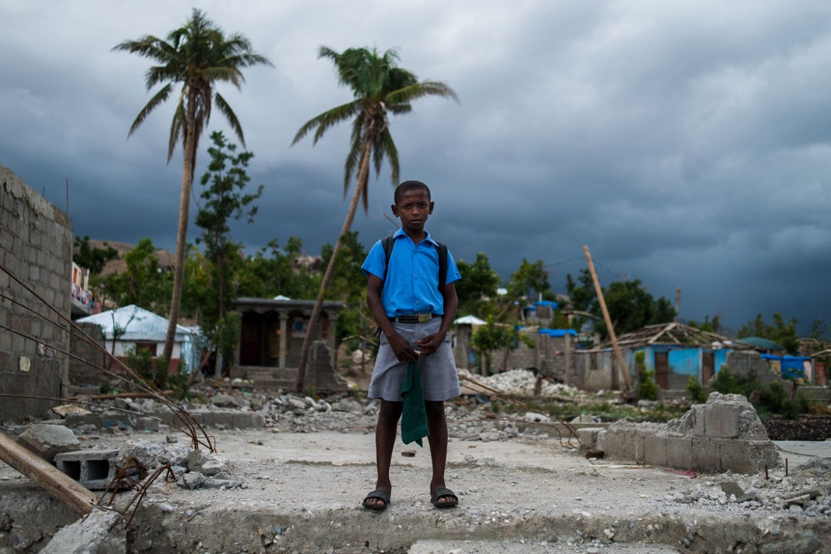 A young boy stands where a schoolhouse once stood before Hurricane Matthew. [Alex McDougall/Al Jazeera]