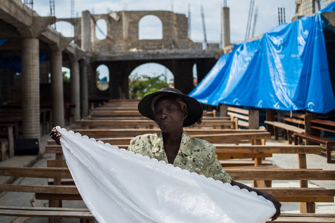 A woman cleans up after a service at Mission Evangelical Baptist Church in Les Anglais. [Alex McDougall/Al Jazeera]