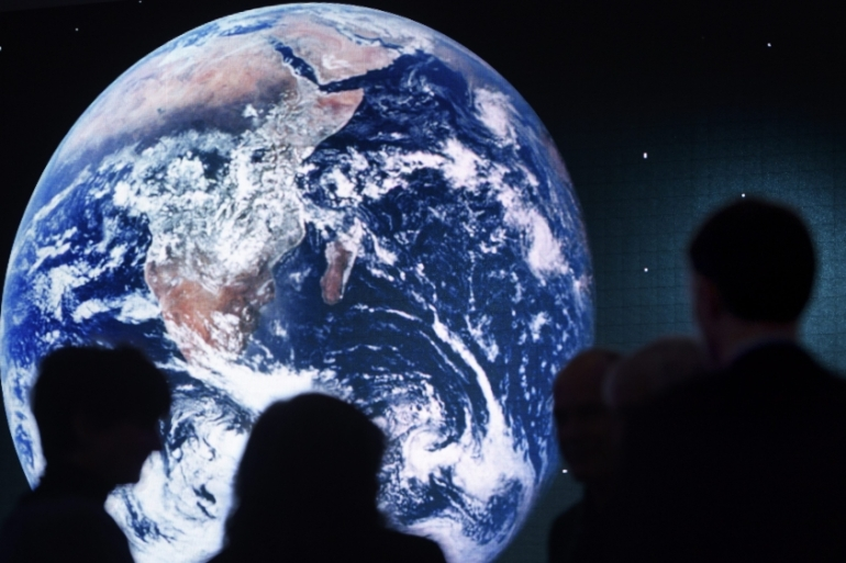 A picture of Earth is shown on a giant screen behind participants of a panel at the World Economic Forum, in Davos in January 2017 [Laurent Gillieron/EPA]