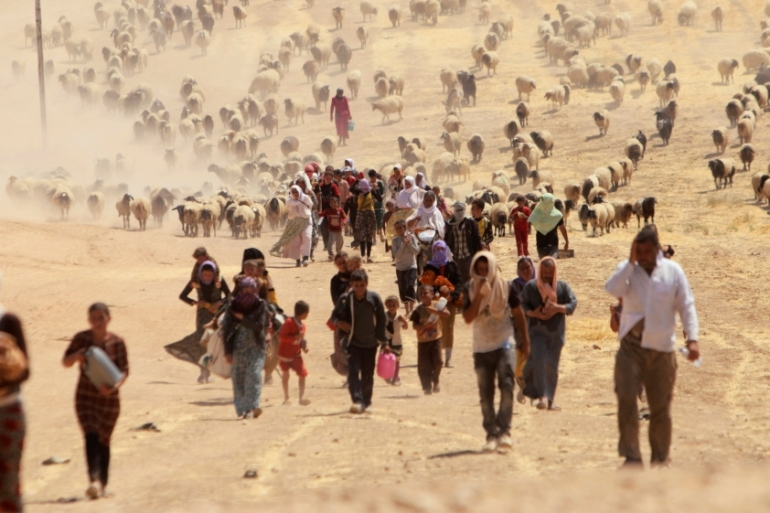 Displaced people from the Yazidi sect flee ISIL towards the Syrian border in August 2014 [File: Reuters]