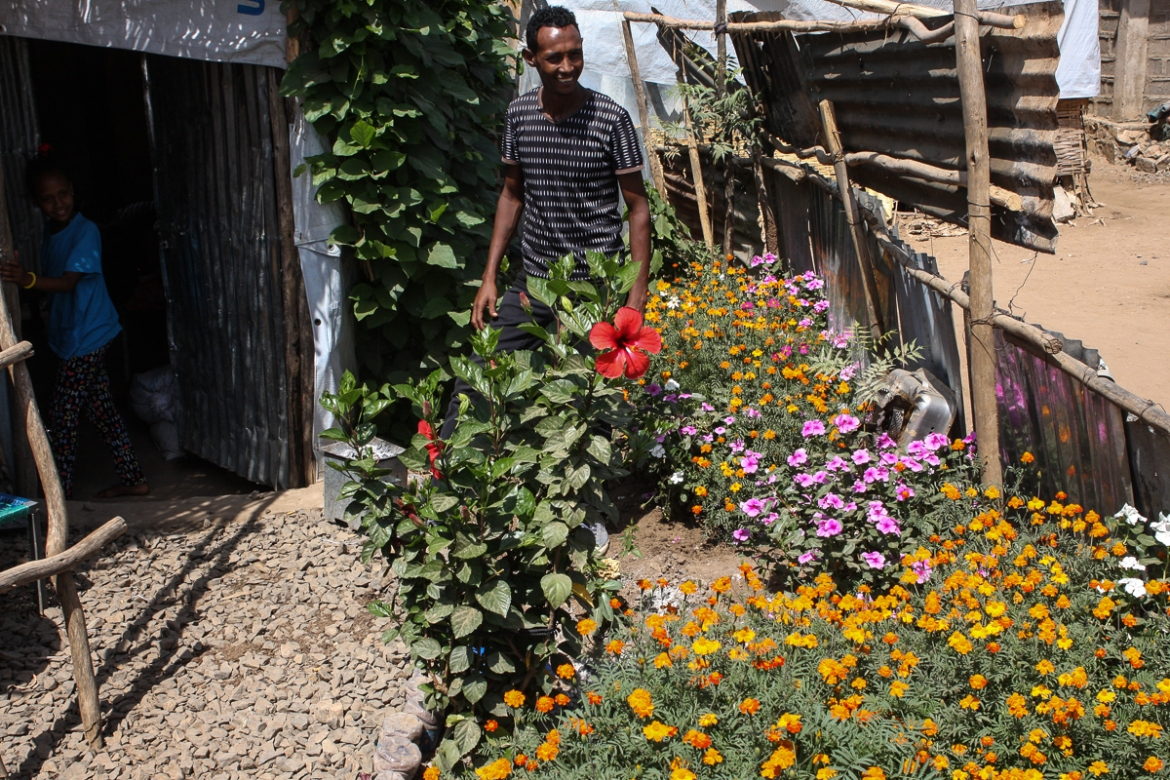 'When I drink a cup of coffee among the flowers it feels good,' says 40-year-old refugee John, proudly showing off the small garden around the Hitsats camp home he shares with his 10-year-old daughter. His wife is in the US. [James Jeffrey/Al Jazeera]
