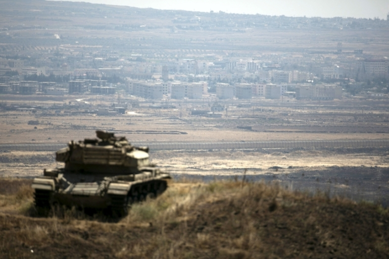 The Syrian area of Quneitra is seen in the background as an Israeli tank parks on a hill, near the ceasefire line between Israel and Syria, in the Israeli-occupied Golan Heights [Reuters]