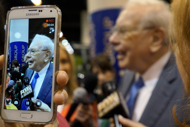 Berkshire Hathaway CEO Warren Buffett is seen on a mobile phone camera as he talks to reporters [Rick Wilking/Reuters/File]