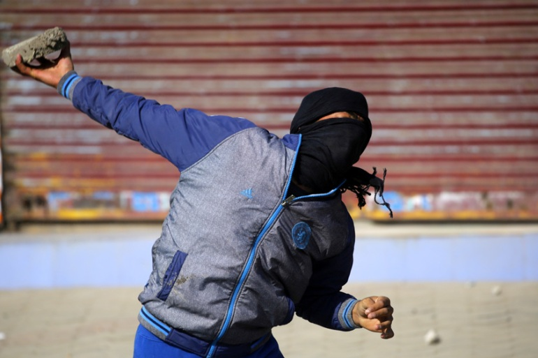 A Kashmiri protester throws a stone at police during clashes in Srinagar last month [Farooq Khan/EPA]