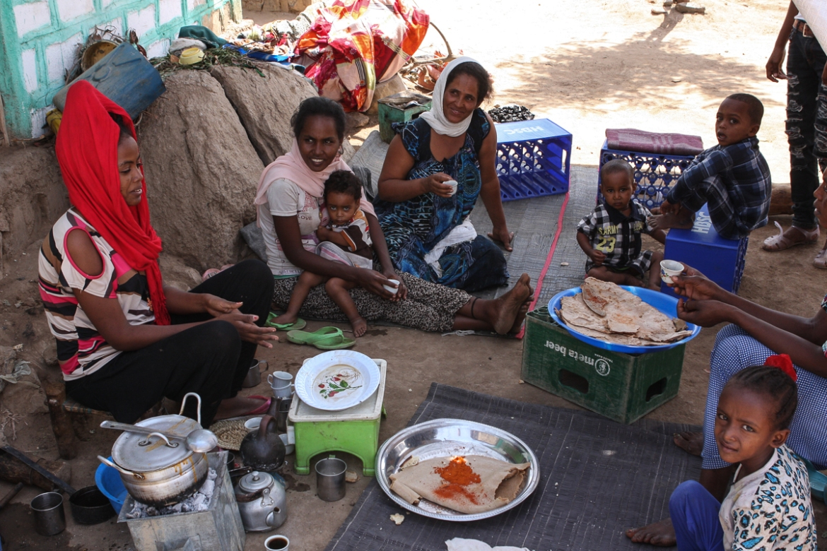 Refugees eat lunch in Hitsats camp. 'I want to go to another country,' says 23-year-old Samrawit. 'I don't dislike it here, but from Ethiopia it's difficult to communicate with my family. From other countries it would be easier.' [James Jeffrey/Al Jazeera]