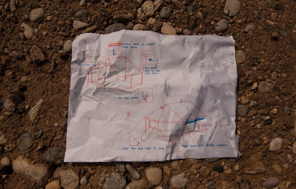 Instructions on how to pitch a tent lie among the foundations in a new camp for displaced people close to Mosul. Each tent can comfortably accommodate six people. Across Iraq, there is room for around 60,000 people in official displacement camps. [Melany Markham/NRC/Al Jazeera]