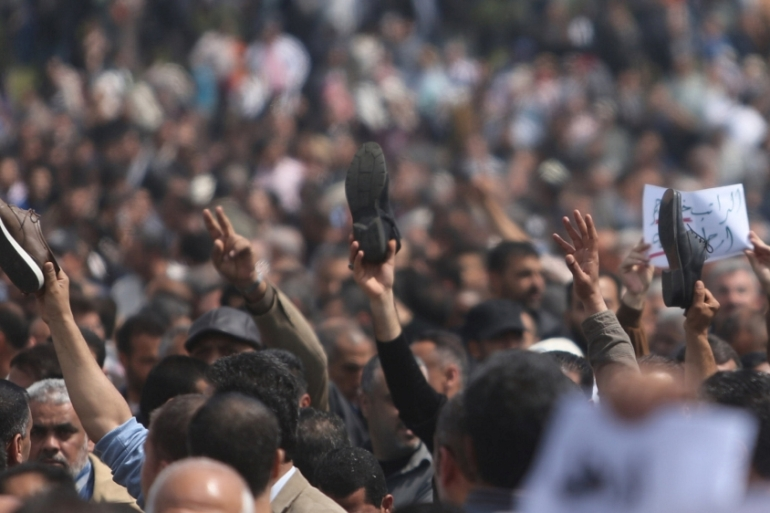 Palestinian Authority employees hold up shoes during a protest against salary cuts [Reuters]