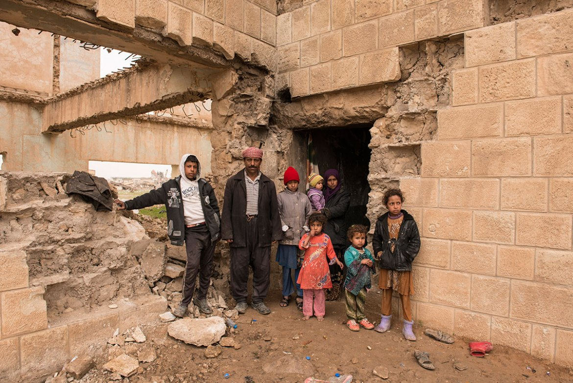 Hamed, his wife and six children live in a building on the outskirts of Hammam al-Alil, which has been badly damaged by explosions. 'It is warm and dry,' he says, as he and his family wait for more permanent accommodation. Families like this will be accommodated in a new camp near Hammam al-Alil that will become home to 30,000 people. [Melany Markham/NRC/Al Jazeera]