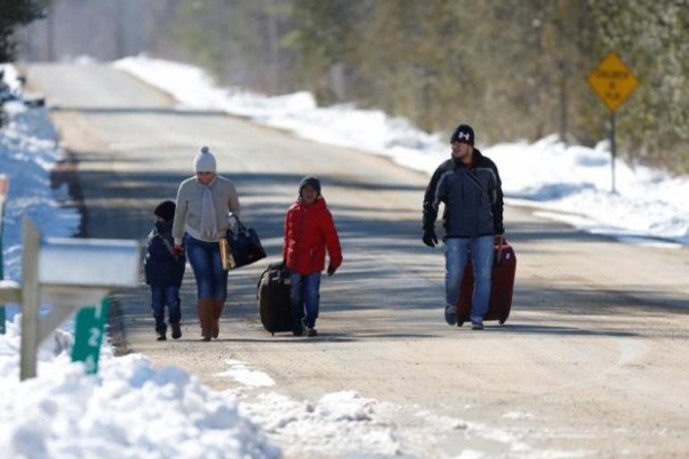 A family who say they are from Colombia walk down Roxham Road towards the US-Canada border [Christinne Muschi/Reuters]