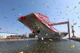 The newly built carrier was transferred from dry dock into the water in Dalian [Li Gang/Xinhua via AP]
