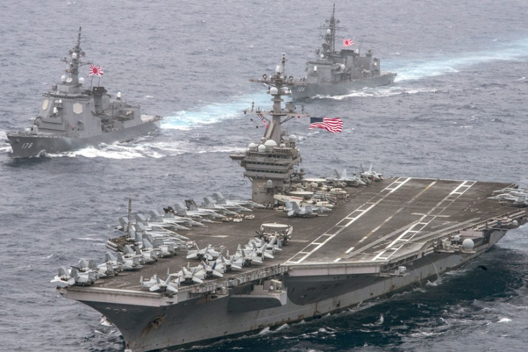 The USS Carl Vinson supercarrier cruises towards the Korean Peninsula escorted by Japanese destroyers [Sean M Castellano/US Navy via AP]