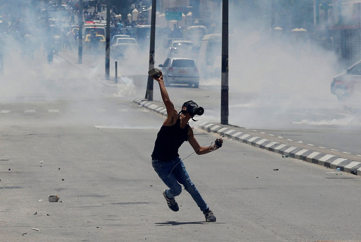 A Palestinian protester hurls stones towards Israeli troops during clashes at a protest marking the 69th anniversary of the Nakba in Bethlehem. [Ammar Awad/Reuters]