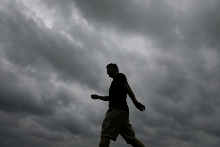 A man walks along a road in Colomboa as storm clouds gather above him [Dinuka Liyanawatte/Reuters]
