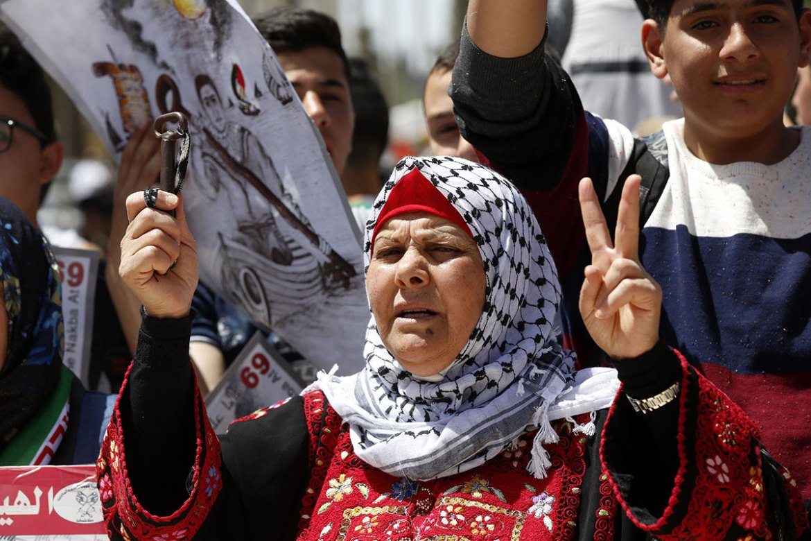 A Palestinian woman holds the key to her old family house as Palestinians stage a Nakba Day rally. [Alaa Badarneh/EPA]