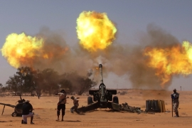 Anti-Qaddafi fighters fire guns at pro-Qaddafi forces near east of Sirte in September 2011 [Asmaa Waguih/Reuters]