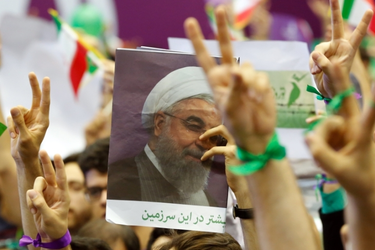 Supporters of Iranian president Hassan Rouhani cheer during an election campaign rally in Tehran [Abedin Taherkenareh/EPA]