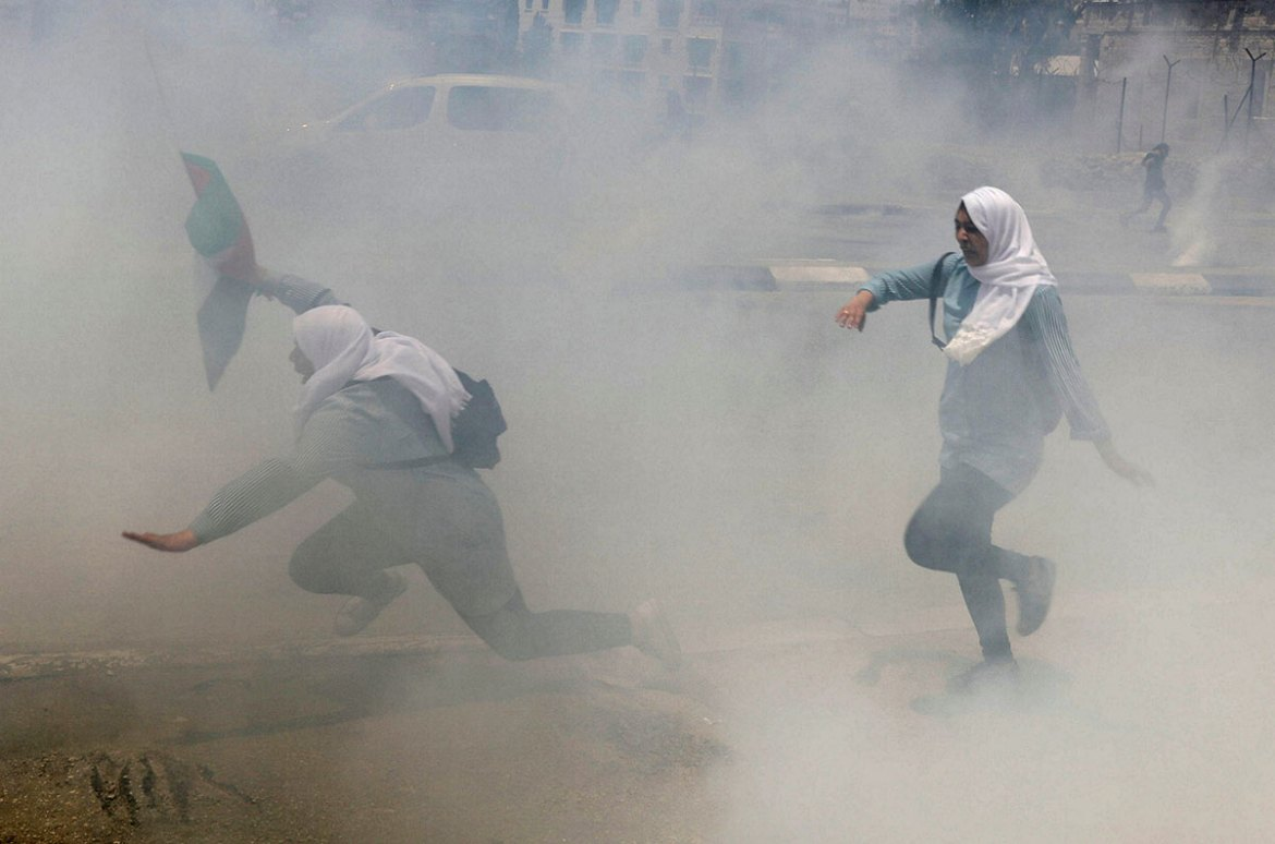 Palestinian schoolgirls run for cover from tear gas fired by Israeli troops during clashes in the occupied West Bank town of Bethlehem. [Ammar Awad/Reuters]