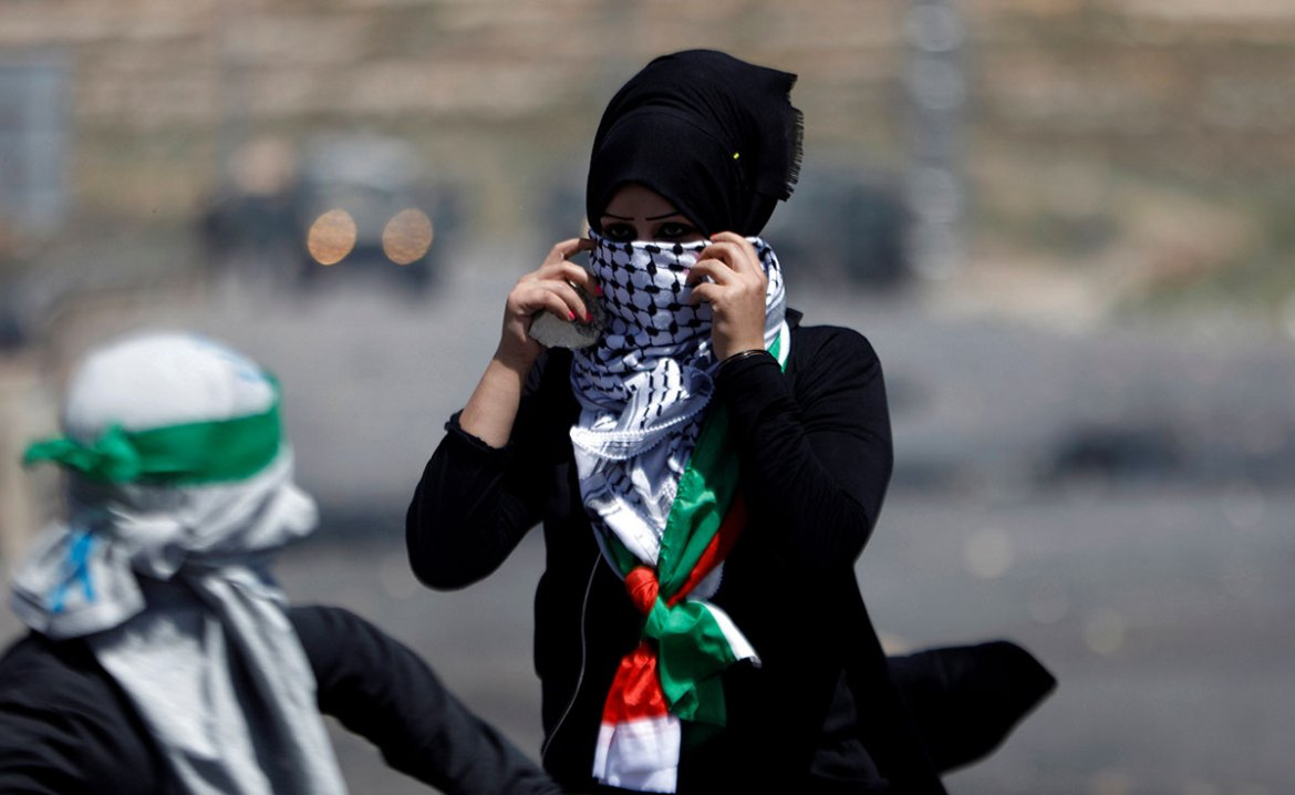 A female protester is seen during clashes with Israeli troops at a protest near the Jewish settlement of Beit El, near the occupied West Bank city of Ramallah. [Mohamad Torokman/Reuters]