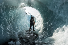 A former ice tunnel is inspected for safety. Compressed blue ice around the sides is as hard as diamond, and much tougher than the fractured white ice at the surface [Alexander Lerche/Al Jazeera]