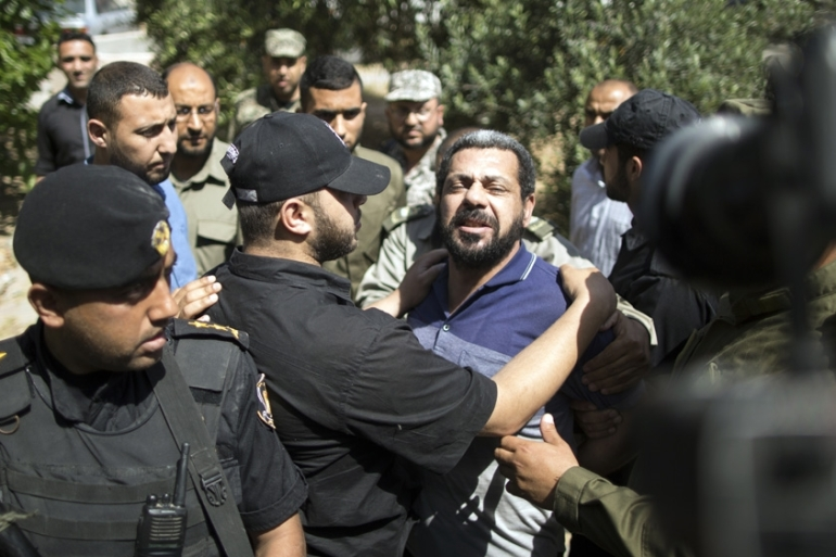Hamas security forces escort Hisham A, centre, out of the military court in Gaza City [Mahmud Hams/AFP]