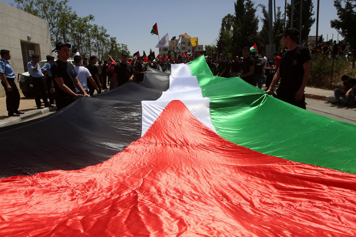 Demonstrators carry Palestinian flags and banners as they stage a rally to mark the 69th anniversary of Nakba Day in the occupied West Bank city of Ramallah. [Alaa Badarneh/EPA]