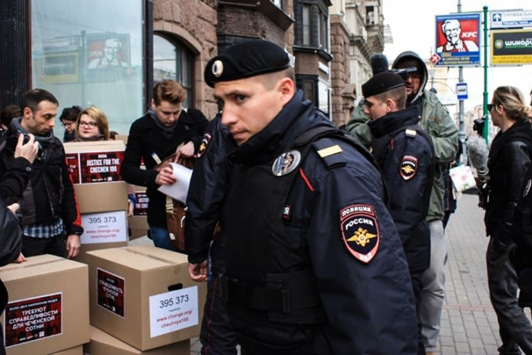 Russian police surround gay-rights activists with boxes of petitions protesting abuses in Chechnya [Marta Khromova/AFP]