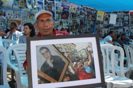 Mahmoud Ziadeh holds a photograph of his son, Majd, who was imprisoned in 2002 [Nigel Wilson/Al Jazeera]