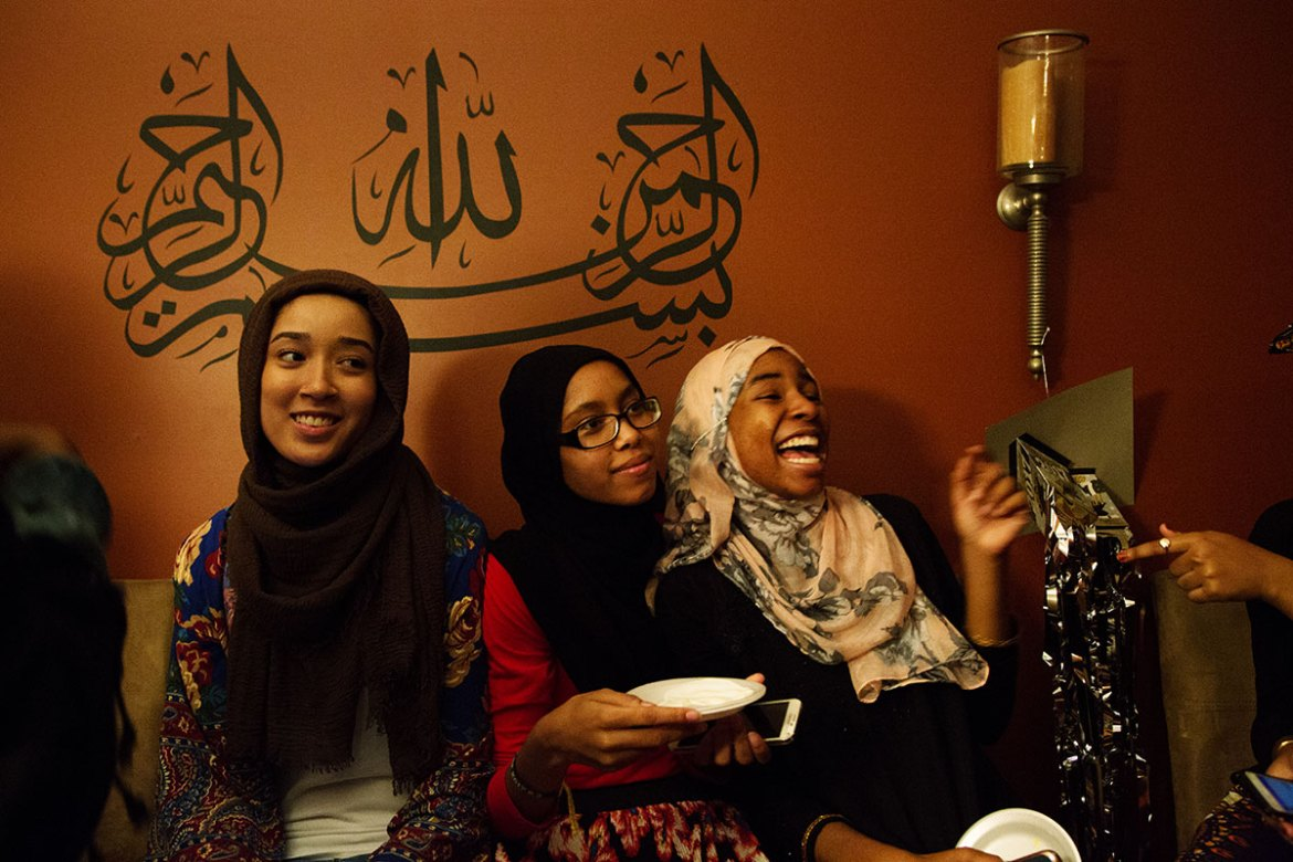 Asiyah, 17, centre, sits among friends at an iftar which also served as her high school graduation party at her family's home. [Annie Risemberg/Al Jazeera]