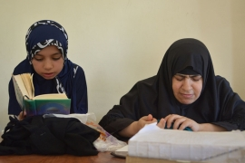 Kareema Abu Shahma (R) reads the Quran next to one of her young students in Khan Younis [Mersiha Gadzo/Al Jazeera]