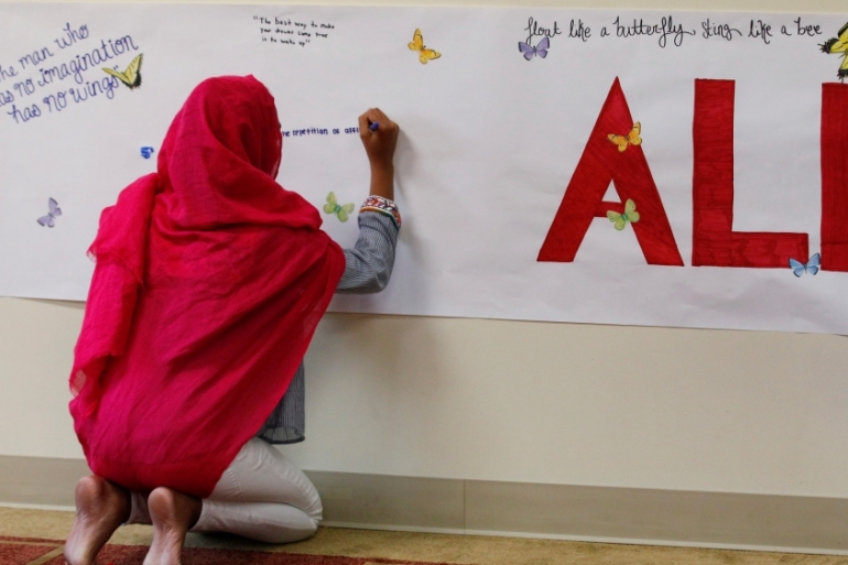 A member of the Louisville Islamic Center writes messages on a memorial banner as she pays her respect to Muhammad Ali in June 2016 [John Sommers/Reuters]