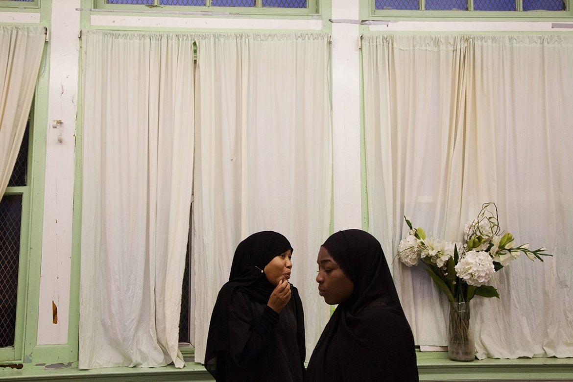 Ayisha, left, and a friend eat dates to break their fast before an iftar meal. As in many parts of the world, Muslims in Philadelphia usually break their daily fast during Ramadan with dates and water before eating a larger meal with the community or with family. [Annie Risemberg/Al Jazeera]
