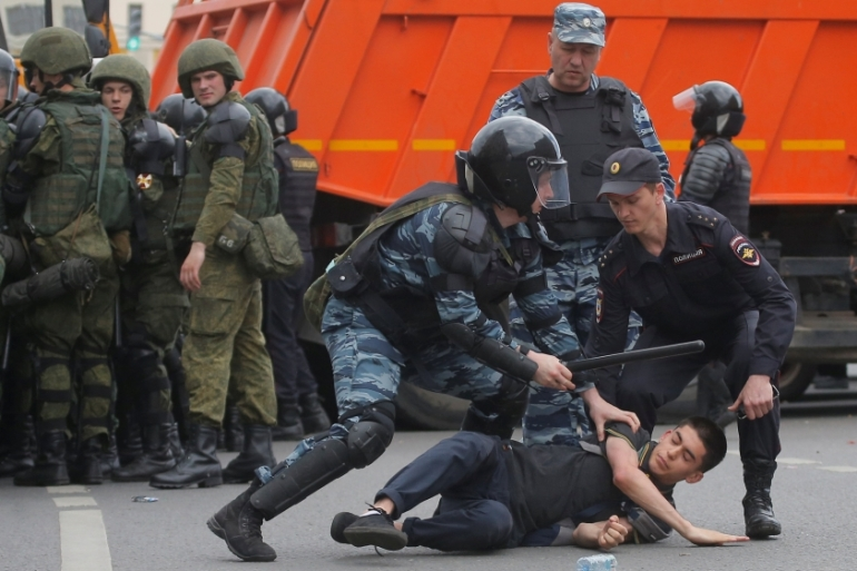 Riot police detain a demonstrator during an anti-corruption protest organised by opposition leader Alexei Navalny, on Tverskaya Street in central Moscow, on June 12 [Maxim Shemetov /Reuters]