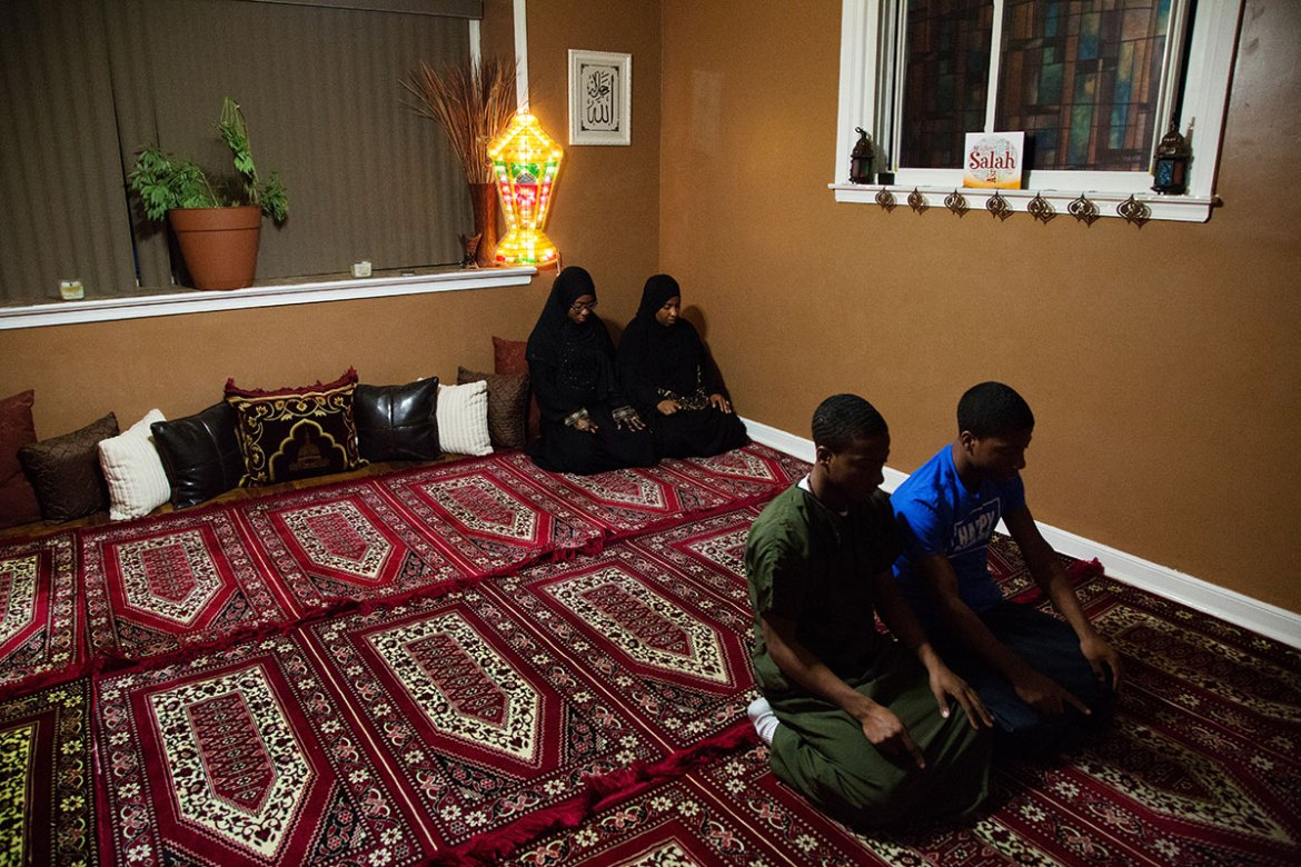 Afeni prays with three of her children - Abdul-Fattah, right, Mukhtar, and Suhaylah, left, in their home. [Annie Risemberg/Al Jazeera]