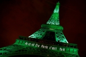 The Eiffel tower is illuminated in green with the words 'Paris Agreement is Done', to celebrate the Paris UN COP21 Climate Change agreement in November 2016 [Jacky Naegelen/Reuters]