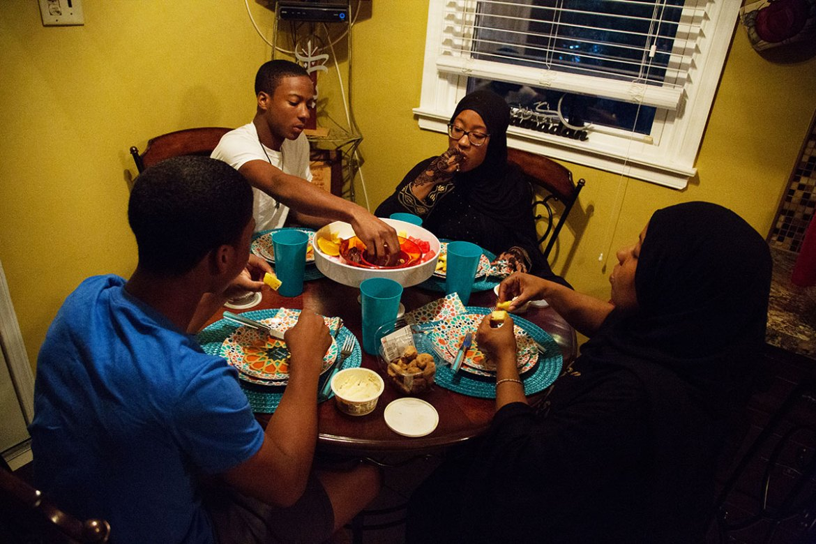 Afeni and three of her children (from left, Abdul-Fattah, Mukhtar, and Suhaylah) break their fast in their home in Philadelphia. Some local mosques offer community iftars, but most often, breaking of the daily fast is done with family in the home. [Annie Risemberg/Al Jazeera]