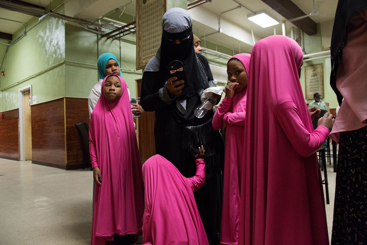 Four sisters dressed in matching outfits wait in line with their mother to be served food at the cafeteria in Philadelphia Masjid. Philadelphia Masjid hosts community iftars every evening during Ramadan, sometimes feeding up to 300 people. [Annie Risemberg/Al Jazeera]