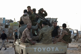 Members of forces loyal to former general Khalifa Haftar ride in a truck in the Benina area, east of Benghazi [Reuters]