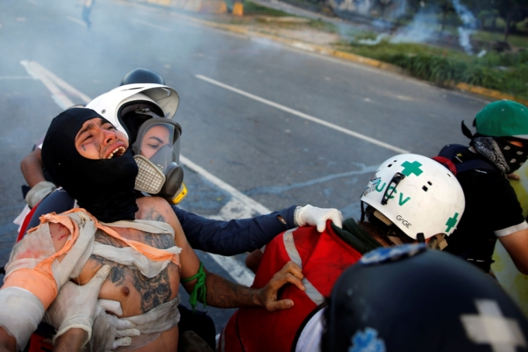 An injured opposition supporter is helped by volunteer medics during clashes in Caracas [Ivan Alvarado/Reuters]