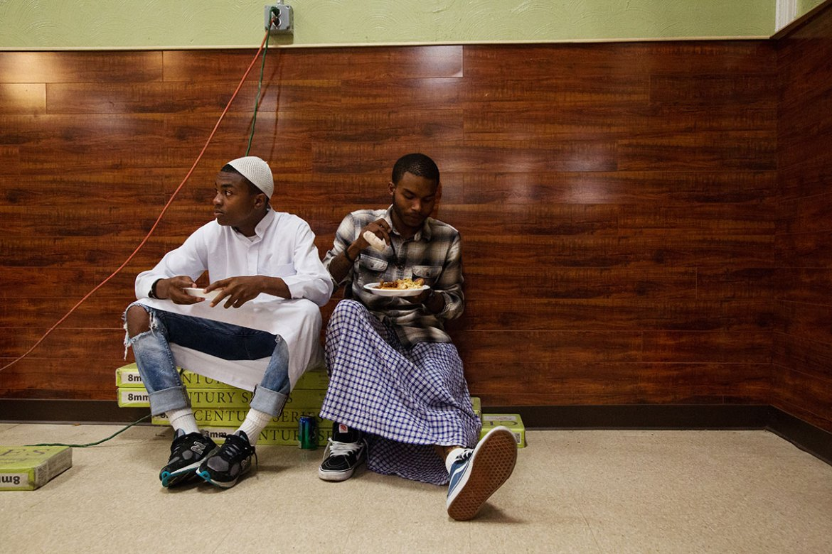 Two young men eat an iftar meal together. It is common for young people in the city to mix urban and Islamic fashion in a manner similar to what is seen here. [Annie Risemberg/Al Jazeera]