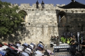 Israeli border police officers stand guard as Muslim men pray outside the Al Aqsa Mosque compound, in Jerusalem [AP Photo/Mahmoud Illean]