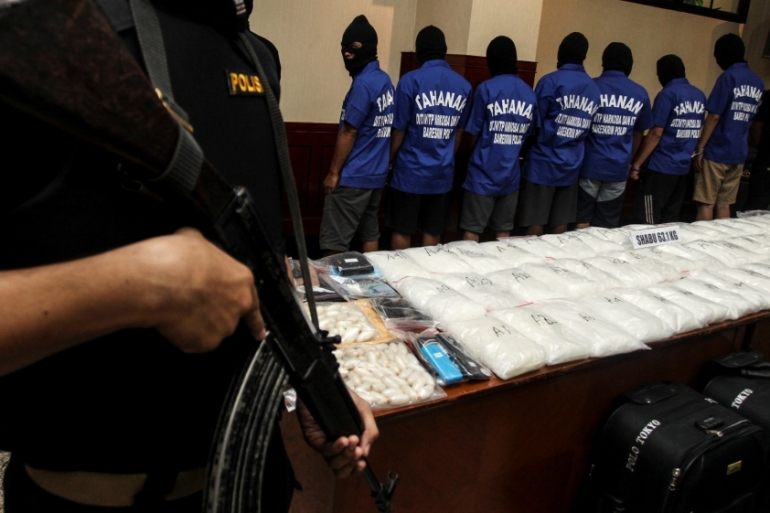 Police present suspects and packets of methamphetamine as evidence to the media following a narcotics raid in Jakarta [Reuters]