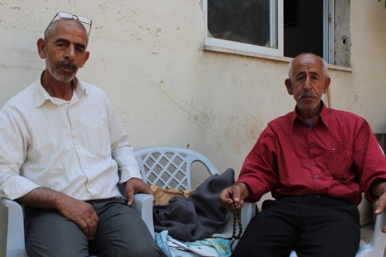 Two of the attacker's family members, Abed al-Abed and Ali al-Abed, sit outside their Kobar home, which has been ordered to be demolished [Nigel Wilson/Al Jazeera]