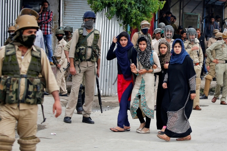 Women walk past police during clashes with stone pelters in Srinagar, Kashmir [Reuters/Cathal McNaughton]