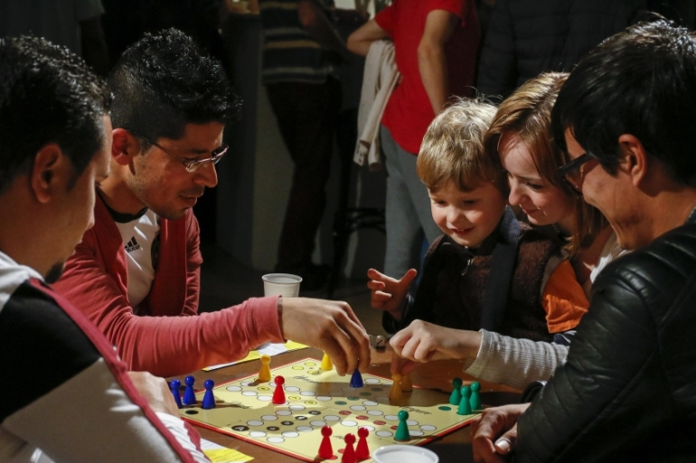 At the international cafe in Dresden, locals and refugees play the German board game 'Mensch Argere Dich Nicht,' which means, 'Do Not Get Angry' [Daniel Koch/Staatsschauspiel Dresden]