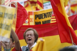 Spain's unionist protesters fly Catalan and Spanish flags during Spain's National Day at Catalonia Square in Barcelona. The banner reads 'Bridges, not walls' [Albert Gea/Reuters]