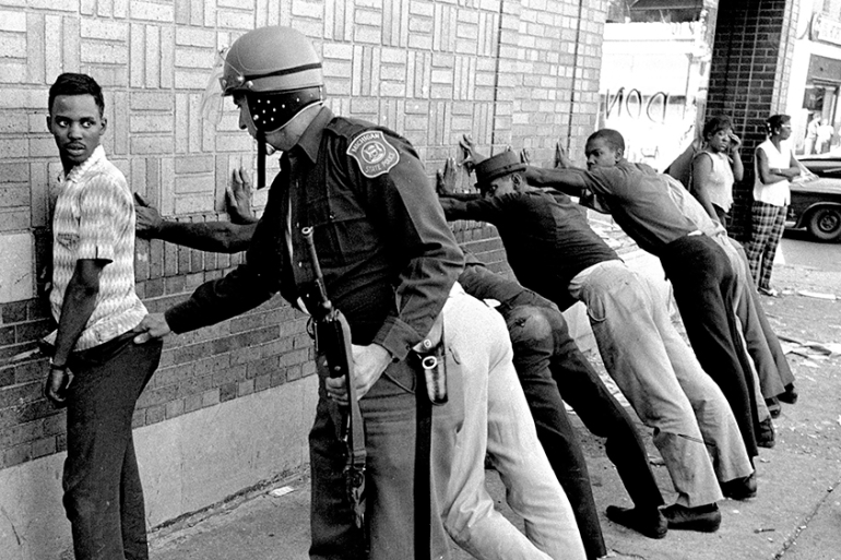 July 24, 1967: Michigan State police officer searches a youth on Detroit''s 12th Street where looting was still in progress after the previous day''s rioting [File photo/The Associated Press]