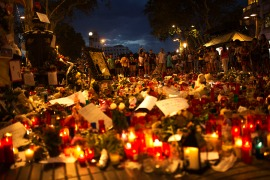 People stand next to candles and flowers placed on the ground for the victims of an attack that left many killed and wounded in Barcelona, Spain [Francisco Seco/AP]